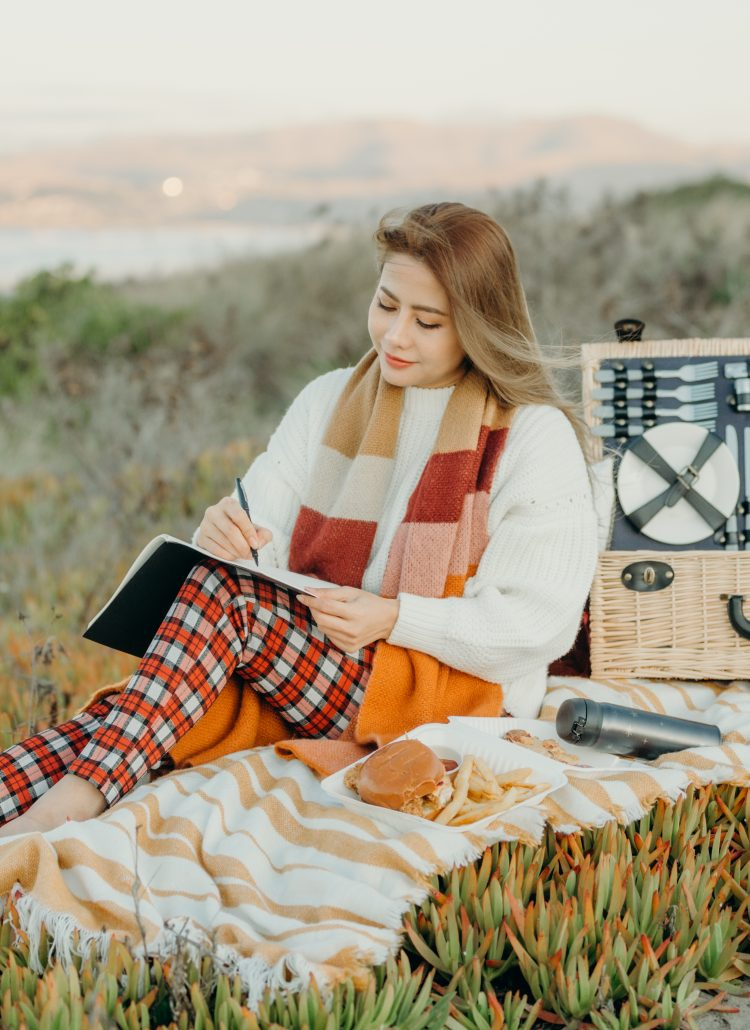 Happy Woman Life Style, beautiful asian girl on the nature picnic with pizza and burger. Relaxing asian woman in Nature at beach. Autumn landscape background. Active Outdoor Relax in Nature.